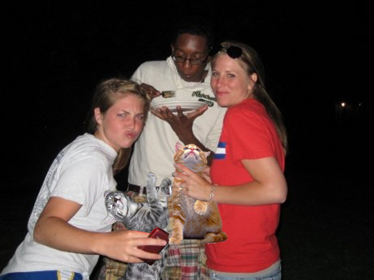 the girl in the white shirt is pretty talented.  she is holding a boozecat and a cell phone in the same hand WHILE making a ridiculous face.  is there anything she can't do?