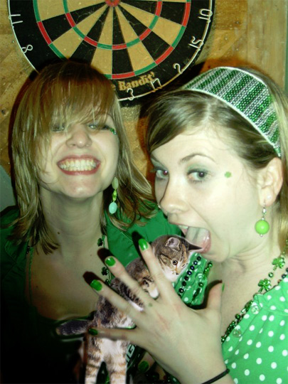 these girls should not be standing so close to that dartboard. in fact there shouldn't even be a dartboard in that bar on st. patty's day.  seems like the most dangerous combination in the world